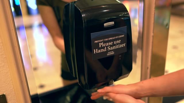 woman using automatic commercial hand sanitizer machine video
