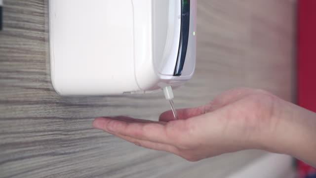 vídeos y material grabado en eventos de stock de mujer que usa un dispensador automático de desinfectante de manos para la prevención de infecciones - hand sanitizer