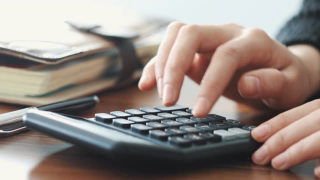 Woman using calculator close up view
