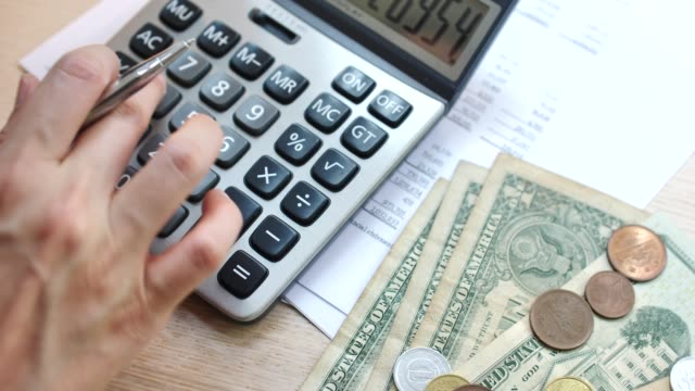 Woman Using Calculator For Taxes And Budget At Home