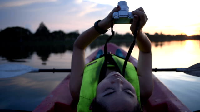 Woman using camera on kayak in twilight evening video