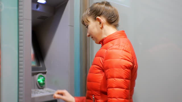 Woman using cash machine. Attractive young female in red bubble jacket inserting credit card into ATM. Woman smiling entering pin code. video