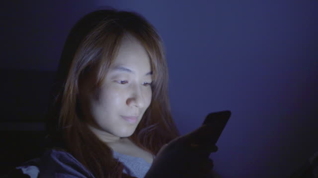 Woman using cellphone in bed at night video