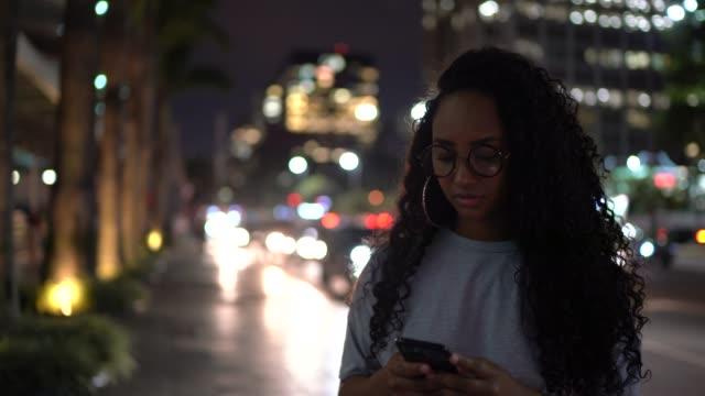 woman using cellphone in the city at night - поколение z стоковые видео и кадры b-roll