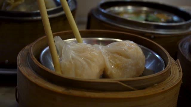 女性レストランで飲茶を食べるための箸を使用しています。伝統的な中国の食糧。 - 中国料理点の映像素材/bロール