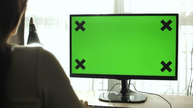 vídeos y material grabado en eventos de stock de mujer usando la pantalla verde de la computadora en casa - computer screen