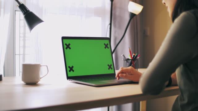女士 :使用電腦筆記本電腦與綠色螢幕在她的辦公桌上在家裡 - laptop 個影片檔及 b 捲影像