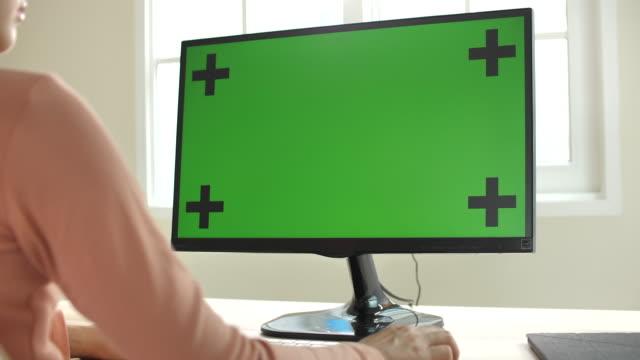 evde yeşil ekranile bilgisayar kullanan kadın - masaüstü bilgisayar stok videoları ve detay görüntü çekimi