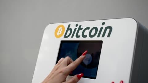 frau mit kryptowährung atm - bitcoin stock-videos und b-roll-filmmaterial