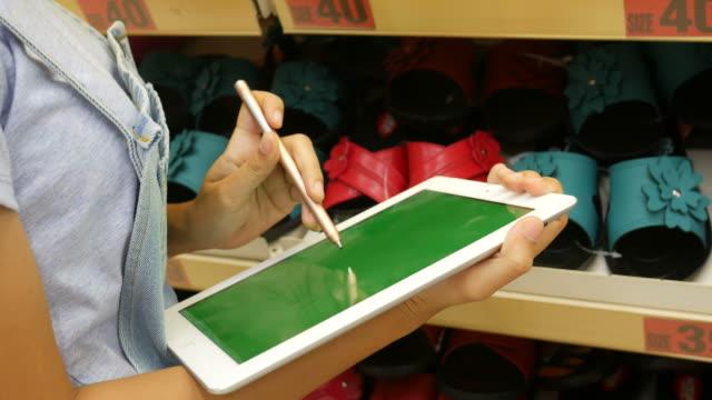 kvinna som använder digital tablett i supermarket - dagligvaruhandel, hylla, bakgrund, blurred bildbanksvideor och videomaterial från bakom kulisserna
