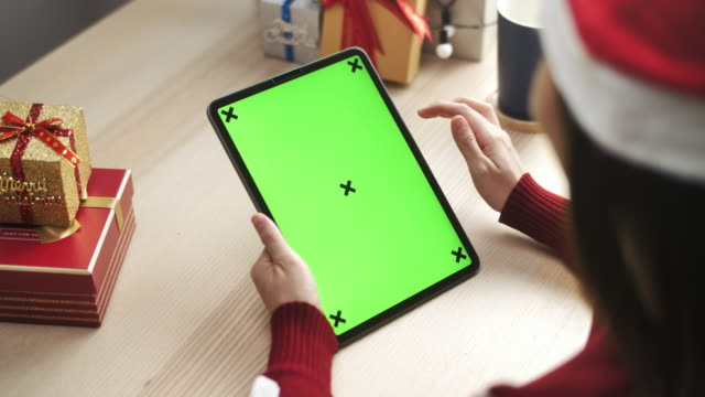 Woman using Digital tablet with green screen in Christmas Event, Vertical