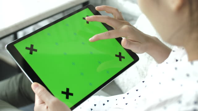 Woman using digital tablet with green screen on monitor, Horizontal