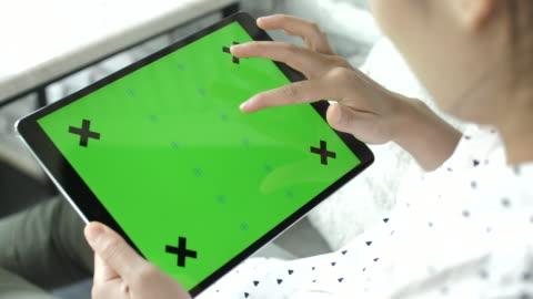 vídeos y material grabado en eventos de stock de mujer usando tableta digital con pantalla verde en el monitor, horizontal - verde color