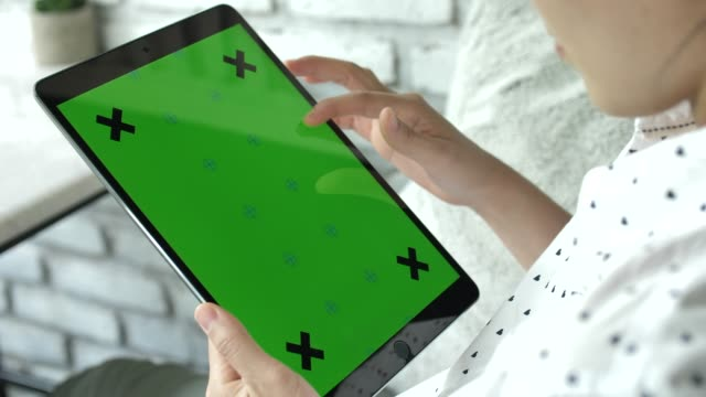 Woman using Digital tablet with green screen