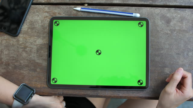 Woman using Digital tablet with Green sreen