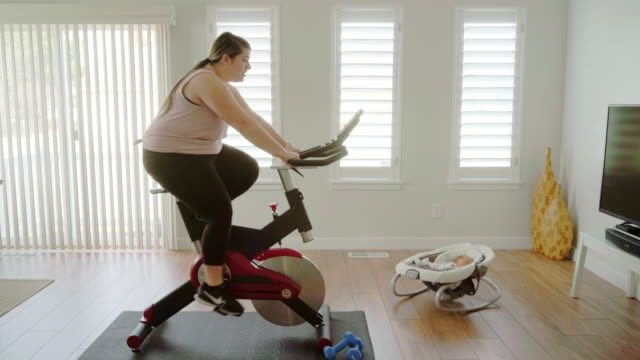 Woman Using Exercise Bike in a Home A woman exercising in her home on an exercise bike. large build stock videos & royalty-free footage