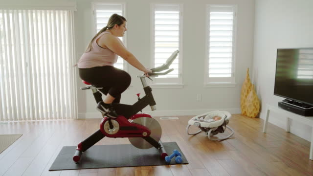 woman using exercise bike in a home - body positive video stock e b–roll