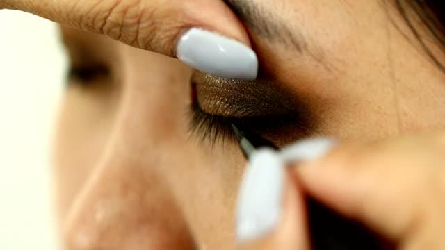 vídeos y material grabado en eventos de stock de mujer usando delineador de ojos maquillaje belleza - ojo morado