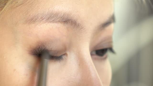 vídeos y material grabado en eventos de stock de sombreador de ojos de mujer con maquillaje belleza colorete - ojo morado