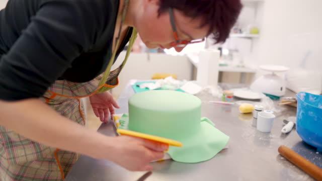 frau mit fondant glatter nach dem bedecken eines kuchens - zuckerguss stock-videos und b-roll-filmmaterial