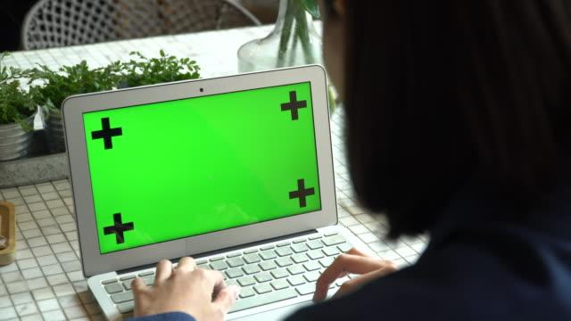 Woman using green screen computer
