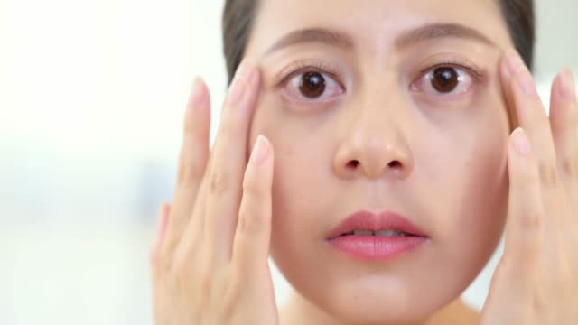 woman using hand caring for eyes. video