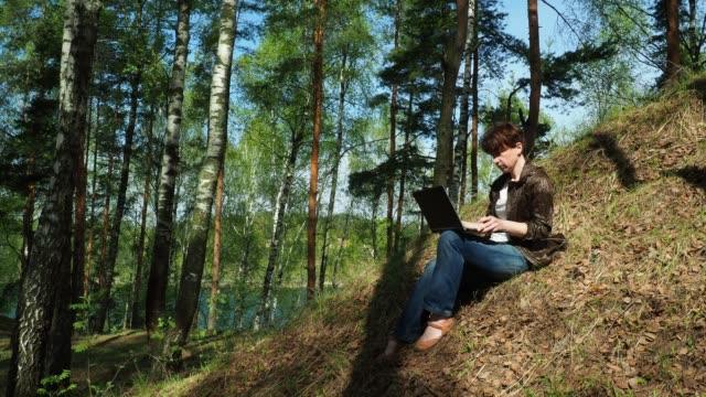 kvinna med sin laptop i skogsmark - endast unga kvinnor bildbanksvideor och videomaterial från bakom kulisserna
