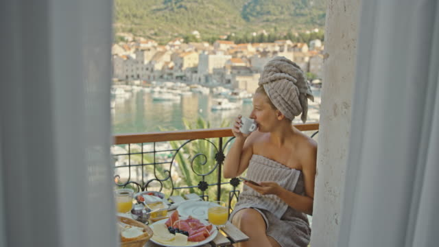 SLO MO Woman using her mobile phone while having breakfast on the balcony by the sea Slow motion shot of a woman using her mobile phone while having breakfast on the balcony by the sea. Croatia. Shoot in 8K resolution mid adult women stock videos & royalty-free footage