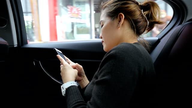 vídeos de stock, filmes e b-roll de mulher usando o celular no carro - dividindo carro