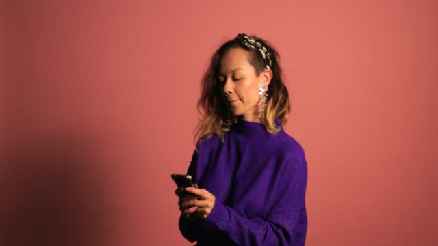 kvinna använder sin smarta telefon - färgad bakgrund bildbanksvideor och videomaterial från bakom kulisserna