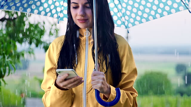 SLO MO Woman using her smartphone in the rain under an umbrella