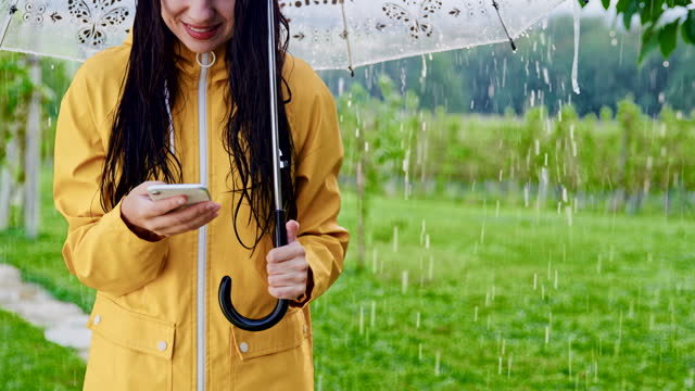 SLO MO Woman using her smartphone while standing in the rain with an umbrella