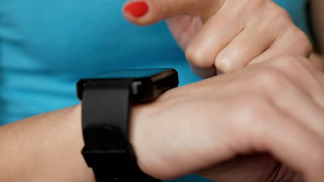 Woman using her smartwatch touchscreen wearable technology device. Woman using her smartwatch touchscreen wearable technology device. Girl making gestures on a wearable smart watch, close up.