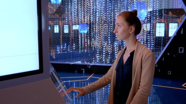 vídeos y material grabado en eventos de stock de mujer usando la pantalla interactiva en exposición de tecnología moderna - exhibir