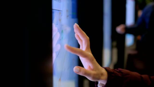 vídeos de stock e filmes b-roll de woman using interactive touchscreen display with city map - ecrã tátil