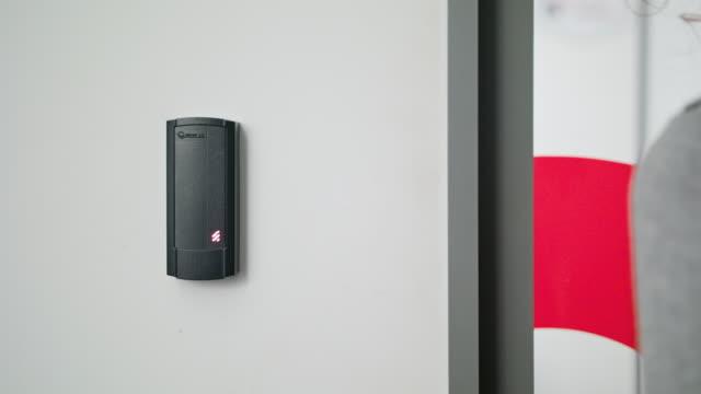 Woman Using Intercom at Residential Building