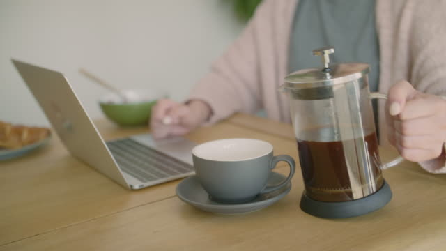 Woman using laptop and pouring coffee from French press video