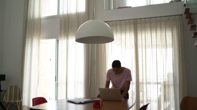 kvinna som använder bärbar dator hemma - endast unga kvinnor bildbanksvideor och videomaterial från bakom kulisserna