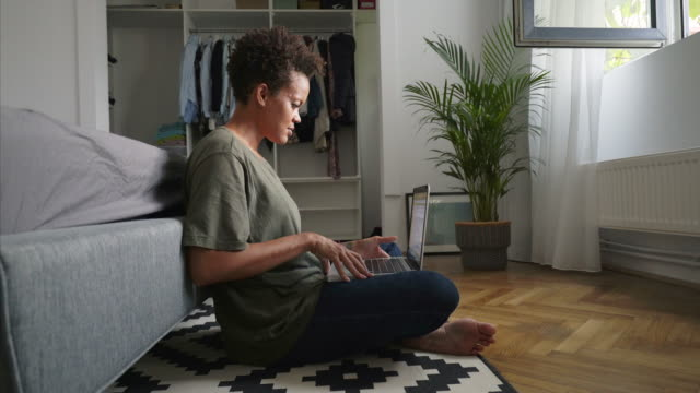 Woman using laptop at home. Woman sitting on the floor using a laptop. She may surf the net, working to a new project or studying. adult stock videos & royalty-free footage
