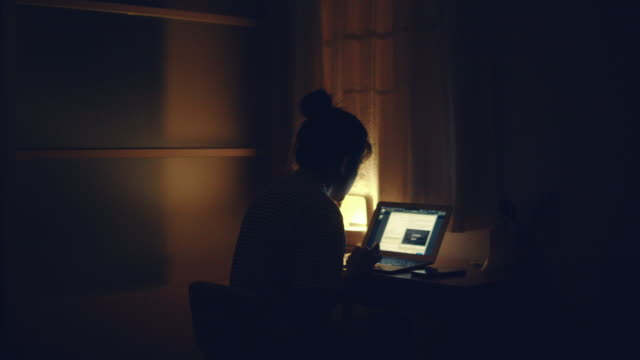 woman using laptop at night - edificio residenziale video stock e b–roll