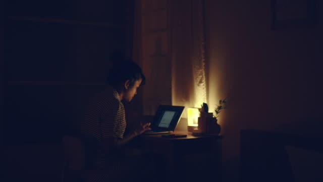 woman using laptop at night - работа допоздна стоковые видео и кадры b-roll