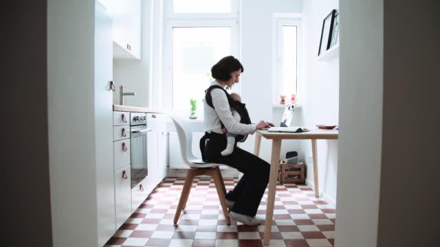kvinna som använder laptop i lägenhet kök med baby i carrier - working from home bildbanksvideor och videomaterial från bakom kulisserna