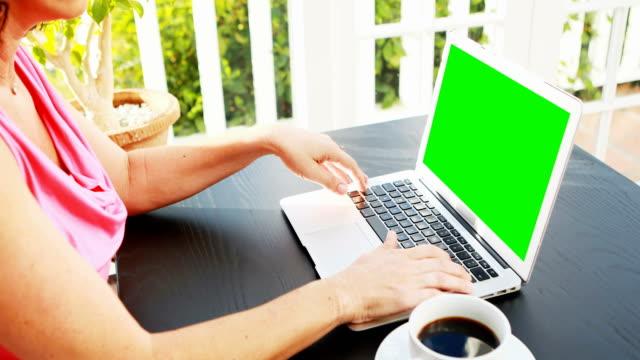 Woman using laptop in restaurant video