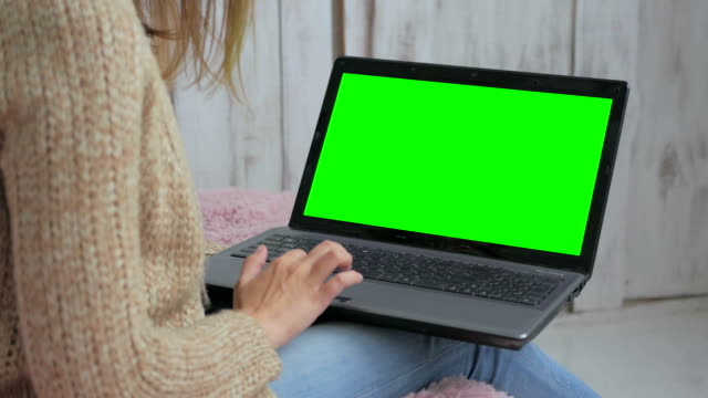 Woman using laptop with green screen video