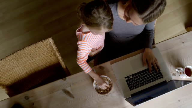 Woman using laptop with nosy daughter video