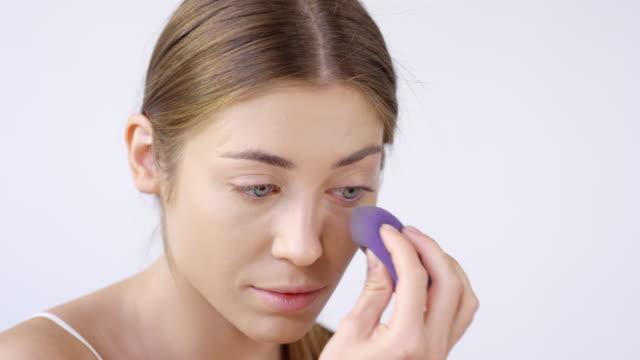 vídeos de stock e filmes b-roll de woman using makeup sponge to blend concealer - esponja