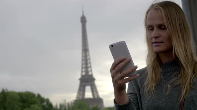 Woman using mobile and taking shot of Eiffel Tower video