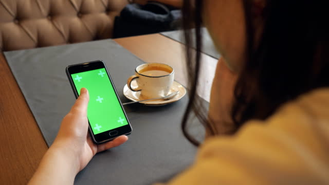 woman using mobile cell phone with green touch screen in cafe woman using mobile cell phone with green touch screen in cafe, close-up tapping stock videos & royalty-free footage