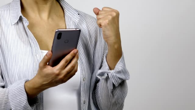 Woman using mobile phone and celebrating achievement and good news Woman in smart casual clothing uses mobile phone. She gets a good news and raises her arm and fist to show happiness good news stock videos & royalty-free footage