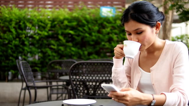 Woman using mobile phone and drinking coffee video